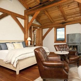 Modelo de dormitorio rústico, grande, con paredes blancas, suelo de madera en tonos medios, chimenea tradicional, marco de chimenea de metal y suelo marrón