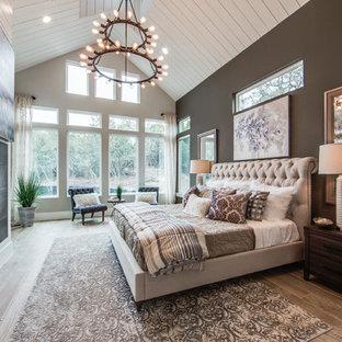 オースティンの広いカントリー風おしゃれな主寝室 (グレーの壁、磁器タイルの床、標準型暖炉、タイルの暖炉まわり、茶色い床) のレイアウト