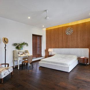 Modern inredning av ett mellanstort sovrum, med bruna väggar, mörkt trägolv och brunt golv