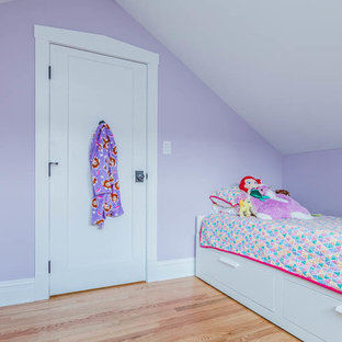 Arts and crafts guest bedroom in Chicago with pink walls, medium hardwood floors and brown floor.