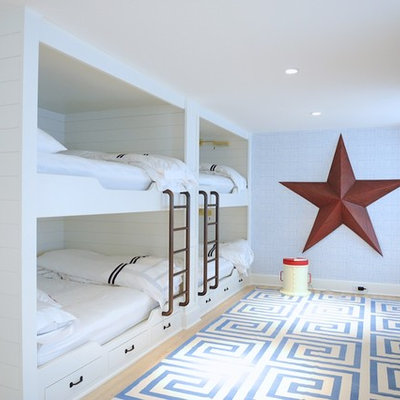 Example of a large beach style guest light wood floor and beige floor bedroom design in New York with blue walls