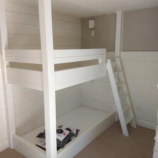 Cette image montre une chambre marine de taille moyenne avec un mur beige, aucune cheminée, un sol beige et du lambris de bois.