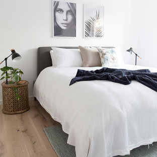 Beach style bedroom in Brisbane with white walls and light hardwood floors.