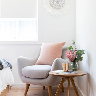 Inspiration for a beach style bedroom in Brisbane with white walls and light hardwood floors.