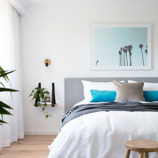 Design ideas for a beach style bedroom in Brisbane with white walls and light hardwood floors.