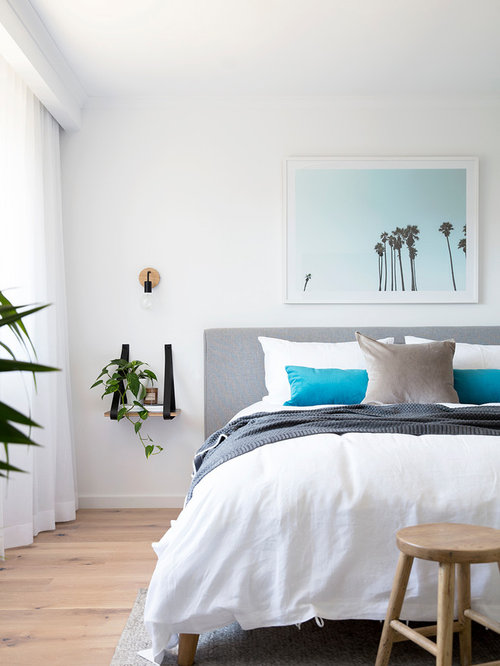 Beach Style Bedroom Design Ideas  Renovations   Photos Design ideas for a beach style bedroom in Brisbane with white walls and  light hardwood floors. Beach Style Bedroom. Home Design Ideas