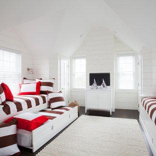 Foto de habitación de invitados costera, sin chimenea, con paredes blancas y suelo de madera oscura