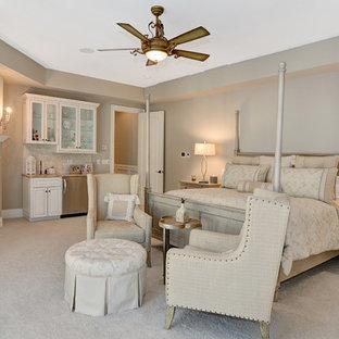Idee per una grande camera matrimoniale con pareti beige, moquette, camino classico, cornice del camino in legno e pavimento beige