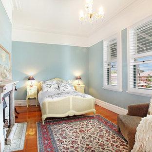 Foto di una camera matrimoniale vittoriana con pareti blu, parquet chiaro, camino classico e cornice del camino in pietra