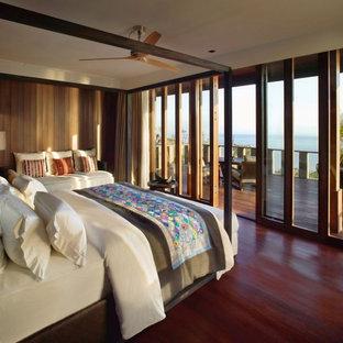 Imagen de habitación de invitados actual, pequeña, con paredes marrones, suelo de madera en tonos medios y suelo rojo