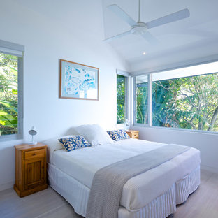Inspiration for a mid-sized beach style guest bedroom in Sydney with white walls, light hardwood floors and beige floor.