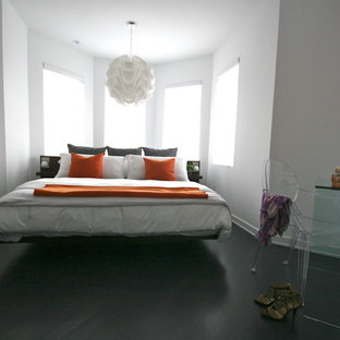 Example of a minimalist black floor bedroom design in Toronto with white walls
