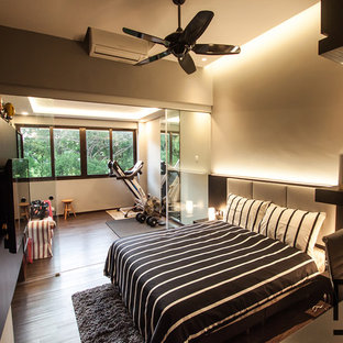 Large modern guest bedroom in Singapore with grey walls and dark hardwood flooring.