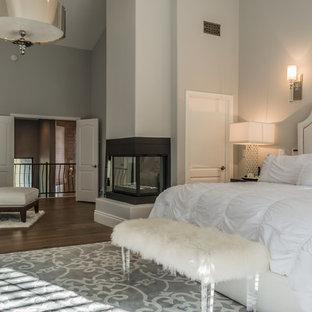 ロサンゼルスの大きいコンテンポラリースタイルのおしゃれな主寝室 (グレーの壁、濃色無垢フローリング、コーナー設置型暖炉、漆喰の暖炉まわり、茶色い床)