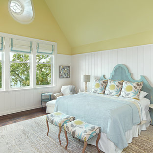 Design ideas for a beach style bedroom in Other with yellow walls, medium hardwood floors and brown floor.