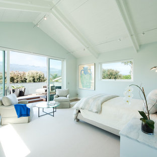 This is an example of a large beach style master bedroom in Santa Barbara with grey walls, medium hardwood floors, no fireplace and brown floor.