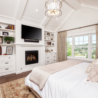 Imagen de dormitorio principal, de estilo americano, grande, con paredes blancas, suelo de madera oscura, chimenea tradicional y marco de chimenea de madera