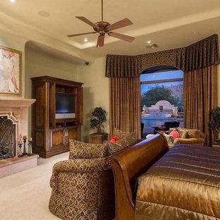 Ispirazione per un'ampia camera degli ospiti mediterranea con pareti beige, moquette, camino classico, cornice del camino in cemento e pavimento beige