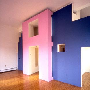 Diseño de dormitorio tipo loft, moderno, de tamaño medio, con suelo de madera en tonos medios, chimenea tradicional y marco de chimenea de yeso