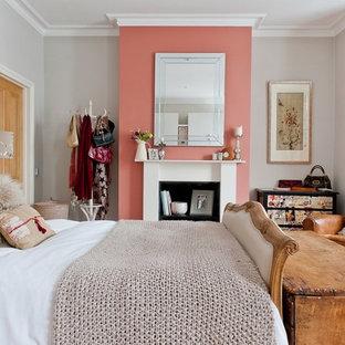 Modelo de dormitorio principal, romántico, de tamaño medio, con paredes rosas, moqueta, chimenea tradicional, marco de chimenea de madera y suelo beige