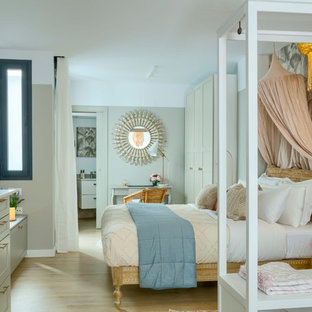 Photo of a mid-sized eclectic loft-style bedroom with green walls, porcelain floors and brown floor.