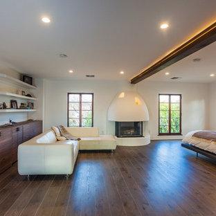 ロサンゼルスの中サイズの地中海スタイルのおしゃれな主寝室 (白い壁、濃色無垢フローリング、標準型暖炉、漆喰の暖炉まわり、茶色い床)