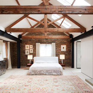 Large industrial master bedroom in London with red walls, light hardwood flooring, a standard fireplace and white floors.
