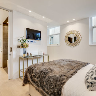 Design ideas for a contemporary bedroom in London with white walls, light hardwood flooring and beige floors.