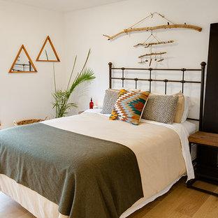 フェニックスの中サイズのサンタフェスタイルのおしゃれな主寝室 (白い壁、無垢フローリング、茶色い床)
