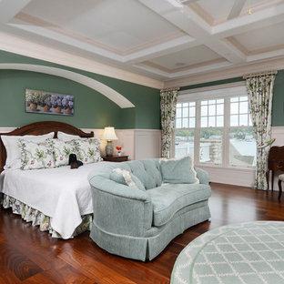 Ejemplo de dormitorio principal, clásico, grande, con paredes verdes, suelo marrón, chimenea tradicional, suelo de madera oscura y marco de chimenea de piedra