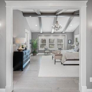 Klassisk inredning av ett mycket stort huvudsovrum, med grå väggar och ljust trägolv