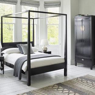 Idées déco pour une grande chambre parentale asiatique avec un mur gris, un sol en bois peint, une cheminée standard et un manteau de cheminée en plâtre.