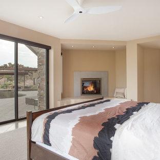 Diseño de dormitorio principal, contemporáneo, grande, con paredes beige, suelo de piedra caliza, chimenea de esquina y marco de chimenea de piedra