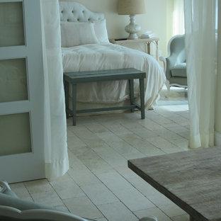 Foto de dormitorio principal, costero, sin chimenea, con paredes blancas y suelo de piedra caliza