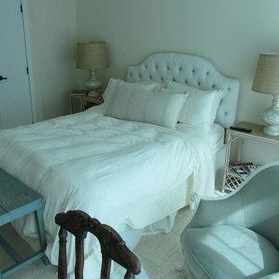 Ejemplo de dormitorio principal, costero, sin chimenea, con paredes blancas y suelo de piedra caliza