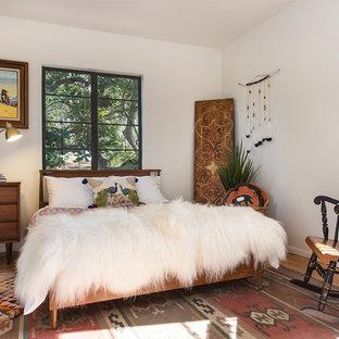 Eclectic guest medium tone wood floor and beige floor bedroom photo in Los Angeles with white walls