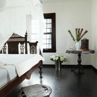 Foto på ett medelhavsstil sovrum, med vita väggar, mörkt trägolv och svart golv
