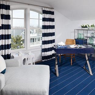 Imagen de dormitorio principal, costero, de tamaño medio, con paredes blancas, suelo de madera oscura, estufa de leña, marco de chimenea de metal y suelo marrón