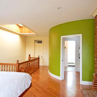 ワシントンD.C.の大きいエクレクティックスタイルのおしゃれなロフト寝室 (緑の壁、無垢フローリング、レンガの暖炉まわり、標準型暖炉、茶色い床) のインテリア