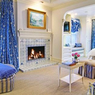 Imagen de habitación de invitados tradicional, de tamaño medio, con paredes blancas, chimenea tradicional, marco de chimenea de baldosas y/o azulejos y moqueta