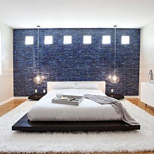 Esempio di una grande camera padronale design con pareti beige e pavimento in legno massello medio
