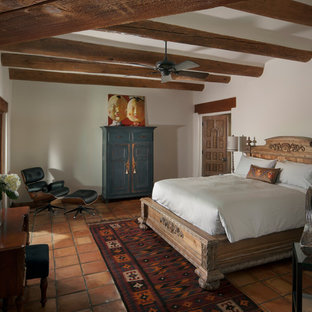 This is an example of a mid-sized country master bedroom in Phoenix with white walls and terra-cotta floors.