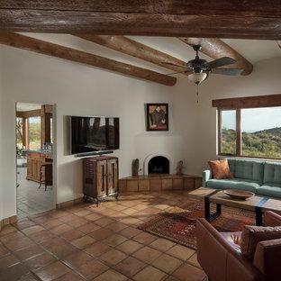 Imagen de dormitorio principal, rural, de tamaño medio, con paredes blancas, suelo de baldosas de terracota, chimenea de esquina y marco de chimenea de yeso
