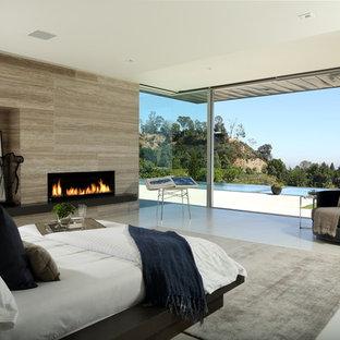 Diseño de dormitorio principal, moderno, extra grande, con paredes beige, suelo de baldosas de cerámica, chimenea lineal, marco de chimenea de baldosas y/o azulejos y suelo beige