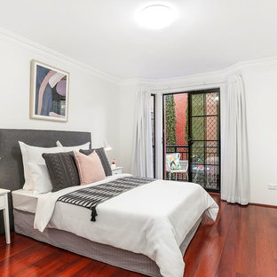 Inspiration for a transitional bedroom in Sydney with white walls, medium hardwood floors and red floor.
