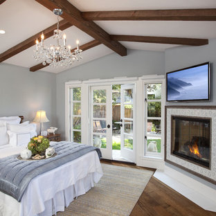Mid-sized traditional master bedroom in San Diego with a corner fireplace, grey walls, dark hardwood floors, a tile fireplace surround and brown floor.