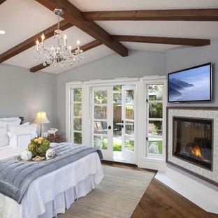 Modelo de dormitorio principal, tradicional, de tamaño medio, con chimenea de esquina, paredes grises, suelo de madera oscura, marco de chimenea de baldosas y/o azulejos y suelo marrón