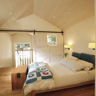 Example of a cottage medium tone wood floor bedroom design in Other with white walls and no fireplace