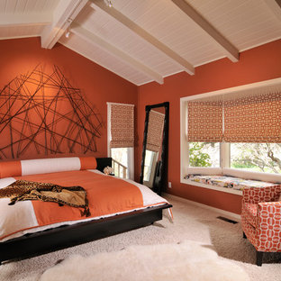 Foto på ett stort vintage huvudsovrum, med orange väggar och heltäckningsmatta
