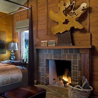 Inspiration for a mid-sized country bedroom in San Francisco with brown walls, slate floors, a standard fireplace and a tile fireplace surround.